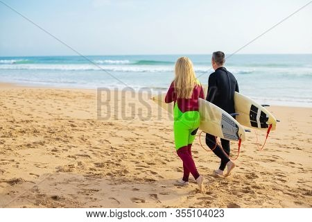 Rear View Of Couple With Surfboards Walking On Beach. Back View Of Man And Woman In Wetsuits Holding