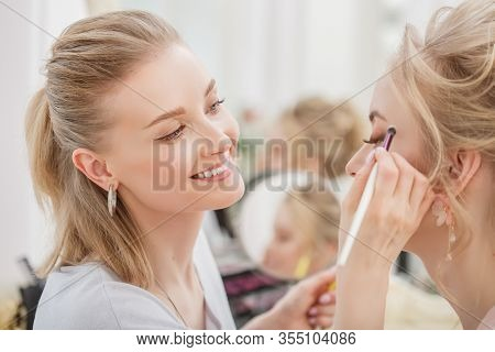 Makeup artist, hair professional stylist makes young beautiful bride bridal makeup before wedding in a morning