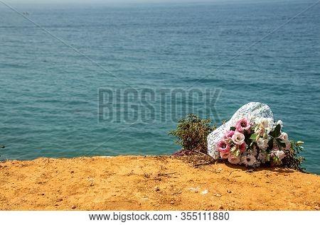 Funeral Flowers At The Beach. Flower Bouquet On Doom Place, Memory, Atlantic Ocean, Spanish Seashoor