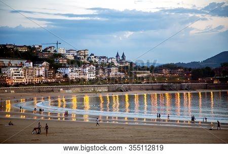 Spain, San Sebastian, May, 12, 2018 - People In The Evening Enjoying Playa De La Concha Beach, Where