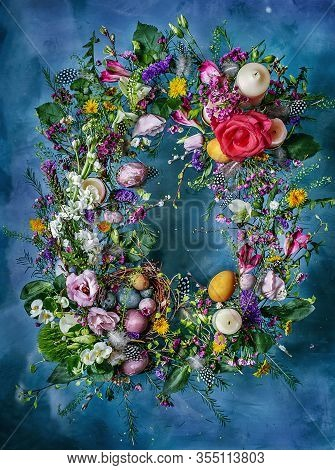 Spring Easter Wreath With Flowers, Herbs, Eggs, Guinea Fowl Feathers And Candles On A Blue Backgroun