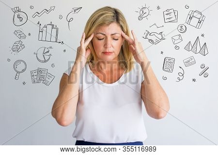 Stressful Woman With Headache And Hand Drawn Business Sketches. Mature Worker Suffering And Touching