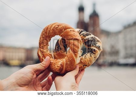 Couple Of Tourists Holding Bagels Obwarzanek Traditional Polish Cuisine Snack On Market Square In Kr