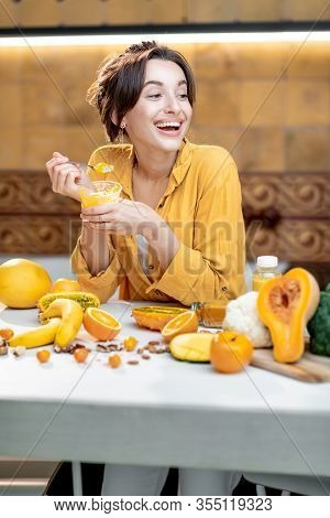 Young And Cheerful Woman Eating Chia Pudding, Having A Snack Or Breakfast In The Kitchen With Lots O