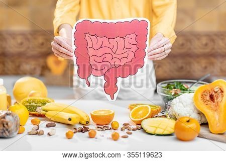 Holding Bowel Model With Variety Of Healthy Fresh Food On The Table. Concept Of Balanced Nutrition F