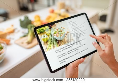 Woman Looking On The Digital Recipe, Using Touchscreen Tablet While Cooking Healthy Meal On The Kitc