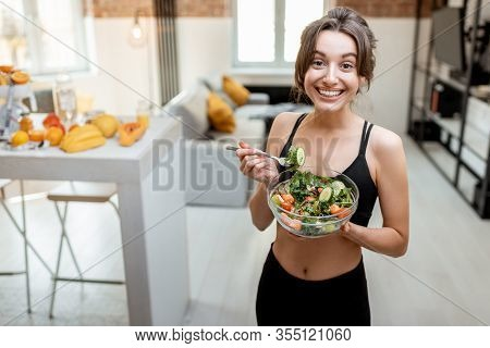 Portrait Of A Cheerful Athletic Woman Eating Healthy Salad During A Break At Home. Concept Of Losing