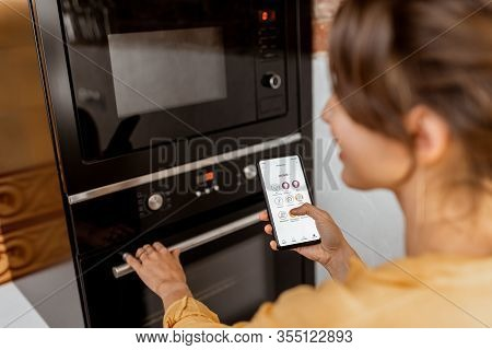 Woman Controlling Smart Kitchen Appliance Using Mobile Phone At Home, Close-up On Mobile Screen. Con