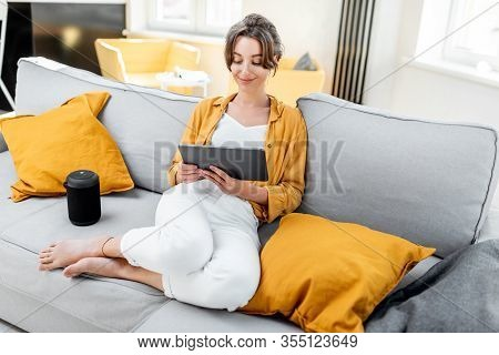 Young And Cheerful Woman Using A Digital Tablet While Sitting Relaxed On The Couch At Home. Concept