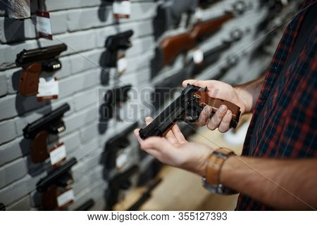 Man holds handgun in gun shop