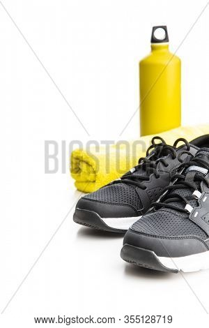 Black sports shoes, towel and bottle isolated on white background.