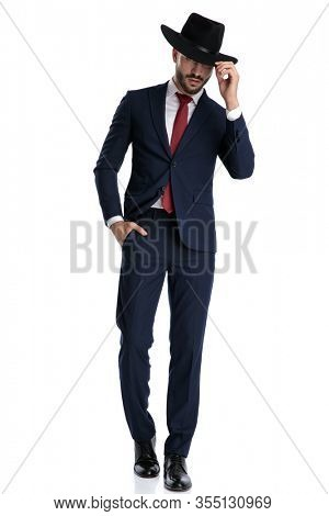 Tough businessman adjusting his hat with his hand in his pocket while wearing suit, stepping confidently on white studio background