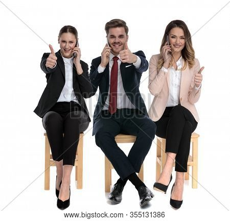 Team of 3 businessmen talking on phone and giving thumbs up while sitting o a chair on white studio background