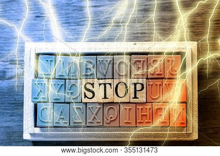 Stop - Isolated Abstract In Blue And Orange Wood Type Stamps And Lightning Or Thunder Against Wooden
