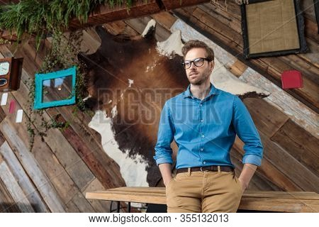 Bothered model looking away and disagreeing with both hands in pockets while wearing blue shirt and glasses, sitting on a desk on coffeeshop background