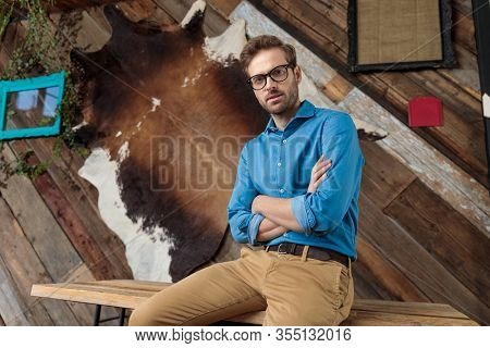 Bothered model holding his hands crossed while wearing blue shirt and glasses, sitting on a desk on coffeeshop background