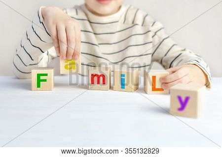 Childs Hands Hold Wooden Cubes With The Colorful Alphabet Made The Word Family On A White Table. The