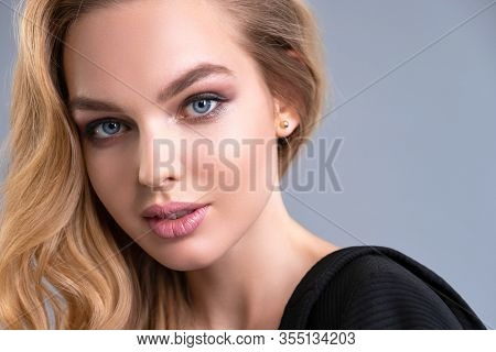 Beautiful face of an attractive model with blue eyes. Woman with beauty long brown hair and natural makeup. Closeup portrait of a caucasian female. Attractive fashion model. Beauty face of a blonde