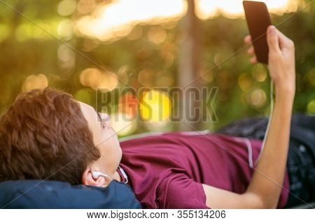 Teen boy with smartphone lies on the bench in the park.   Teenage boy is using phone, outdoors.  Caucasian teenager in casual clothes with cell phone in park. Soft focus effect.