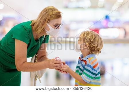 Family With Kids In Face Mask In Shopping Mall Or Airport. Mother And Child Wear Facemask During Cor