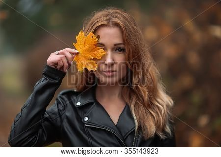 Portrait Of Redhead Woman With Yellow Leaf With Long Curly Hair On Blurred Autumn Background. Girl O