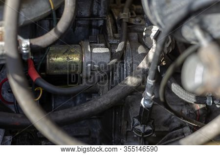 Starter In The Engine Compartment Of An Old Car. Dirty Engine Compartment Of A Gasoline Car. Repair