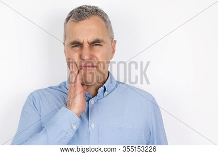 Adult Handsome Man With Grey Hair Wearing Blue Shirt Touching Cheek With Hand Suffering From Sudden
