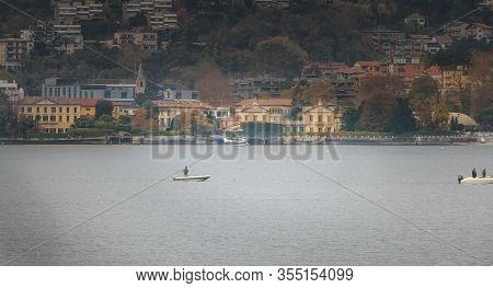 Passenger Seaplane Landing On Lake Como Among Small Fisherman Boats
