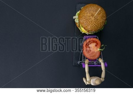 Figurine Of A Little Wooden Man Pushing A Basket Of A Supermarket With A Tomato Next To A Hamburger.