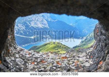 Fedaia Lake In Dolomites Mountains, Italy, As Seen Through A Crenel From An Old War Tunnel.