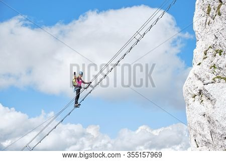 Stairway To Heaven Concept With A Female Climber Holding Her Fist Up And Tight, On The Via Ferrata L