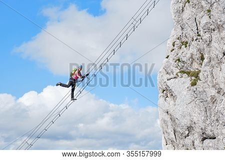 Female Tourist Raising Her Leg On Via Ferrata Route Called Intersport Klettersteig Donnerkogel, In A