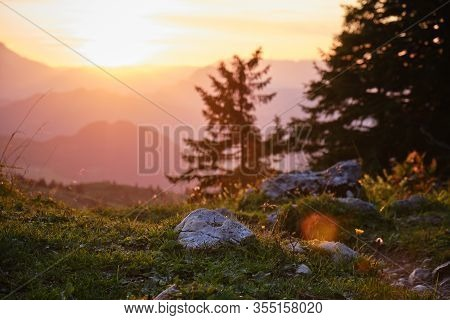 Sunset In The Austrian Alps With Shades Of Orange, Out Of Focus Mountain Layers, And A Stone Near A