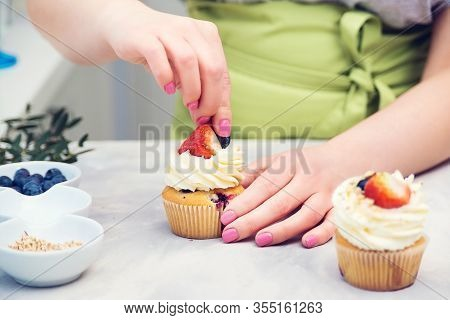 Female Baker Decorating Tasty Cupcake With Berry. Pastry Chef Woman Making Creamy Cakes.