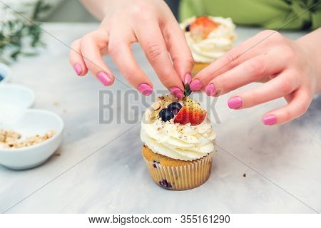 Confectioner Decorate Cupcakes With Cream Cheese And Berries, Close Up. Homemade Pastry. Woman Cooki