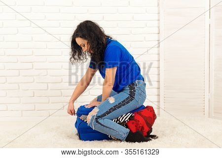 Pretty Girl Is Sitting On Suitcase. Woman Packing A Luggage. A Girl Packing For A Trip. Girl Getting