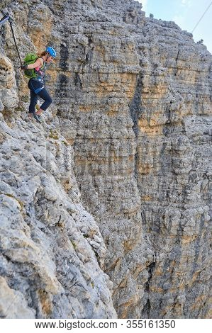 Courageous Female Climber Looking Down From High Up On Via Ferrata Cesare Piazzetta, Dolomites Mount