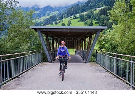 Woman Biking Over A Bridge Along A Cycling Route In Zillertal Valley, Austria.
