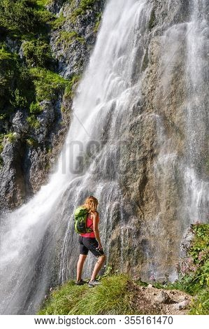 Woman Hiker, With A Green Backpack, Looks Up At Dalfazer Waterfall, Austria.