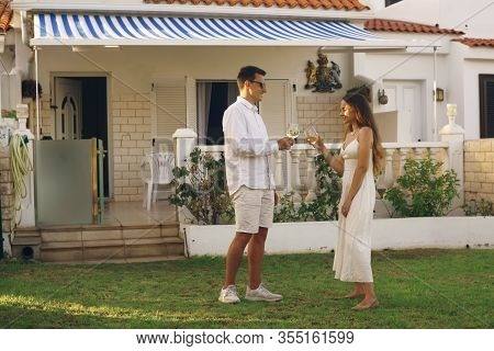 A couple drinks white wine on the lawn near their home on the island. On a trip, the couple rented a