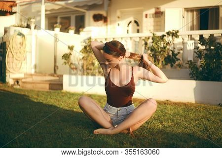 The Girl Does Yoga, Does Exercises, Does Sports On The Lawn Near Her House. Girl In The Early Mornin