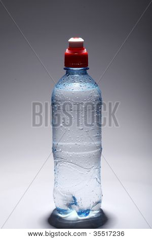 Plastic bottle of fresh and cold water over gray gradient