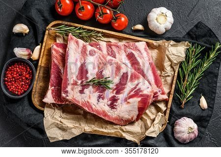 Raw Pork Meat Ribs With Ingredients For Cooking Rosemary And Garlic In A Wooden Bowl. Black Backgrou