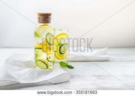 Detox Sassy Water With Lemon, Cucumber And Mint. A Bottle And A Glass Of Clean, Cool And Fresh Drink