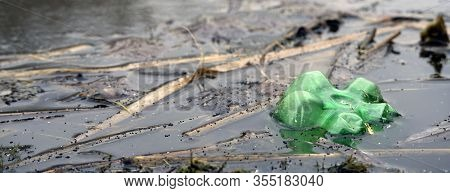 A Green Plastic Bottle Floating In Polluted River Or Lake Water, Environmental Problem With Plastics