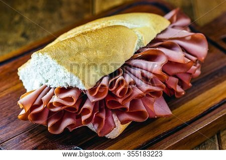 Sliced ​​pork Sandwich. Fatty, Cooked Meat Snack. In Brazil It Is Called Bread With Mortadella.