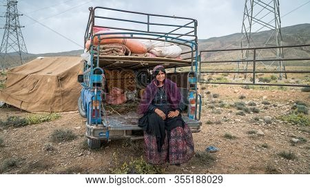 Shiraz, Iran - May 2019: Qashqai Woman Sitting By An Old Car. The Qasqhai Are Nomadic People Living