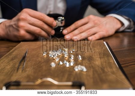 Selective Focus Of Gemstones On Board And Jewelry Appraiser Working At Table Isolated On Grey