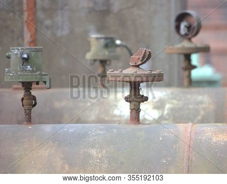 Various Valves On A Large Rusted Pipeline In A Disused Factory
