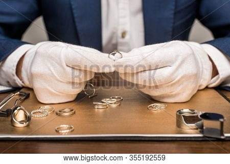 Cropped View Of Jewelry Appraiser Holding Jewelry Ring Near Board And Magnifying Glass On Table Isol